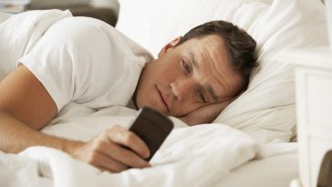 Man In Bed At Home Texting On Mobile Phone