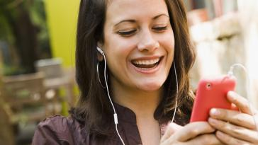 Cropped head-and-shoulders of a smiling young woman listening to her mobile phone with headphones outdoors, perhaps on a phone call or listening to music