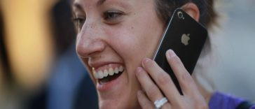 CORAL GABLES, FL - FEBRUARY 10:  Julie Bennink makes a phone call on her new iPhone that she had just purchased at a Verizon Wireless stores after they started selling the smart phone on February 10, 2011 in Coral Gables, Florida. AT&T  had previously had a monopoly on selling the iPhone since 2007.  (Photo by Joe Raedle/Getty Images)